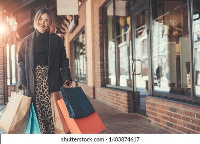 Nice cheerful young model with short haircut hold shopping bags in hands. Looking on camera and smiling. Stand on left side. Alone outside. Beautiful bright day. Sun shines