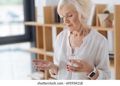 Nice cheerless woman holding a palm with the pill