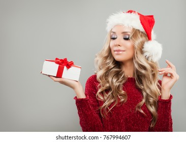 52cb5d4fb6706 Nice Christmas Girl Holding White Christmas Gift Box with Red Ribbon on  Gray Banner Background.