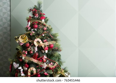 Nice Christmas tree decorated with red, gold and whiter decorations. Preparing for holiday season