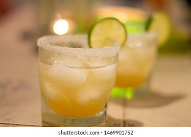 Nice coktail with salt, lime and ice cubes on table decorated with candles. Night atmosphere.