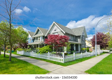 Nice and comfortable neighborhood. A row, line of the houses, homes behind white country style wooden fence in the suburbs of Canada, Vancouver.