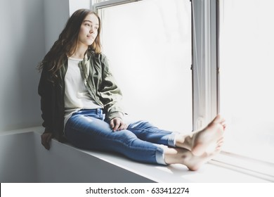 A nice and cool Teenager girl sitting on window