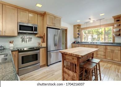 Bonita cocina de madera rústica con isla de madera y azulejos verdes.