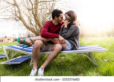 nice couple boyfriends relaxing and hugging sitting on a deckchair in a public park