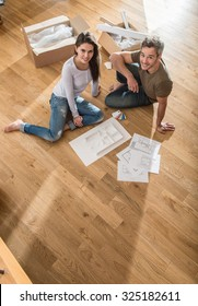 Nice couple casual clothes sitting barefoot stock photo download nice couple in casual clothes sitting barefoot on the wooden floor of their new house malvernweather Choice Image