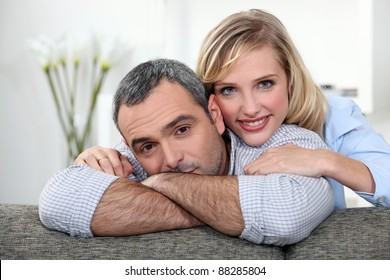 A nice couple cuddling on a couch.
