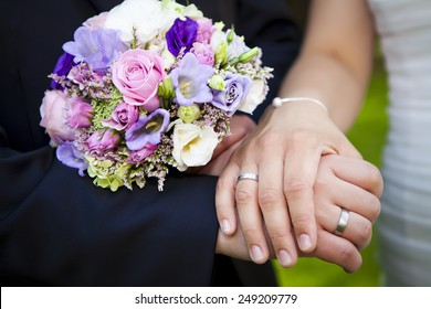 nice couple are showing her hands close p directly after the wedding with their purple roses bridal boquet