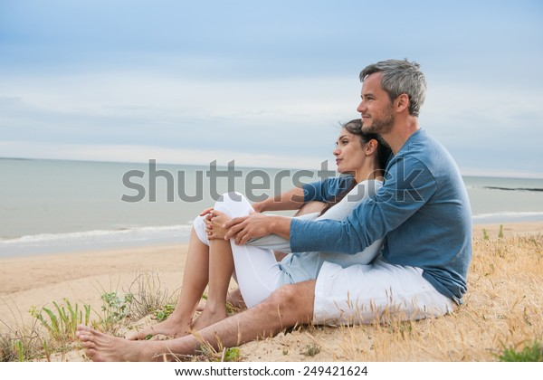 Nice couple sitting in the sand in casual clothes, looking at the ocean