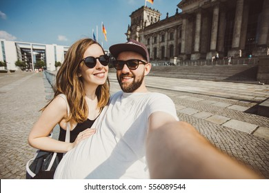 Nice couple of students taking selfie near Reichstag in Berlin. Funny hipster friends taking picture for travel blog in Germany.
