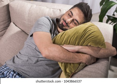 Nice and cozy. Top view of satisfied young man lying and embracing pillow while having nap on sofa