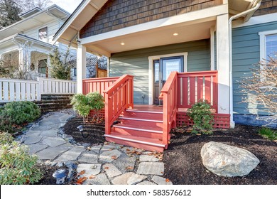 Nice Craftsman home with covered porch accented with red railings and glass stained front door. Northwest, USA