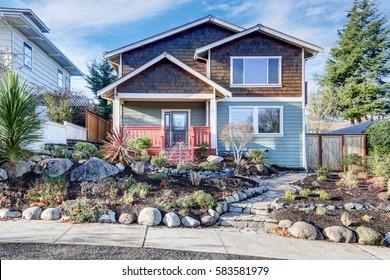 Nice Craftsman home exterior on blue sky background. Well kept frontyard with natural stone landscape design. Northwest, USA