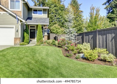 Nice curb appeal of American brand-new house. Well kept front garden with perfect lawn and flower bed. Northwest, USA