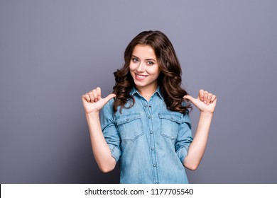 Nice cute cheerful adorable lovely attractive brunette caucasian stylish girl with wavy hair in casual denim shirt, showing, pointing two thumbs at herself, isolated over grey background