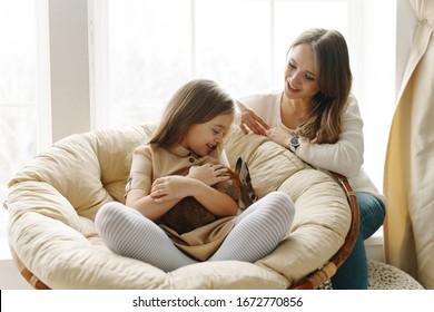 Ein nettes süßes Mädchen und ihre schöne Mutter genießen sonnigen Tag. Familie, die zusammen mit einem Kaninchen in einem hellen, sonnigen Raum spielt