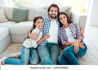 Nice cute lovely sweet tender attractive cheerful people mom dad sitting on floor carpet free time feelings friendship trust wearing jeans denim casual style in light white modern interior indoors