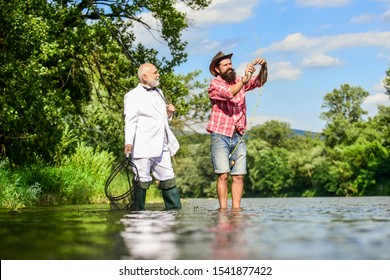 Nice day for fishing. retired father and mature son with beard. Fly fishing adventures. hobby of businessman. retirement fishery. happy fishermen in water. friends men with fishing rod and net.