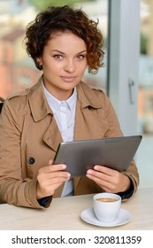 Nice day. Pleasant positive charming girl sitting at the table and holding laptop while drinking coffee