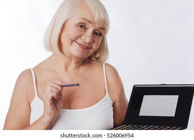 Nice delighted woman applying eyeshadow