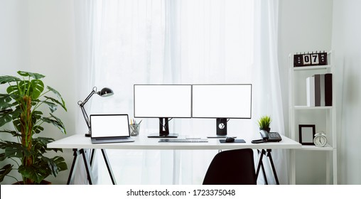 Nice desk in home, computer and laptop with blank screen on table in home on the day light shone in the afternoon.