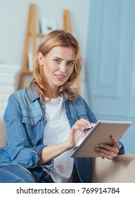 Nice device. Cute lovely young woman feeling relaxed while sitting on a comfortable sofa and using her convenient modern tablet