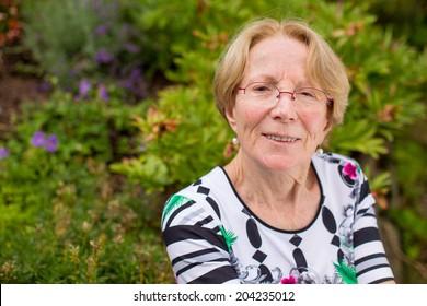 A nice elderly woman is dreaming in a beautiful garden