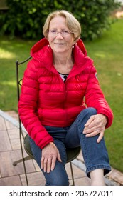A nice elderly woman sits in the garden and smiles into the camera bending one knee and leaning on it