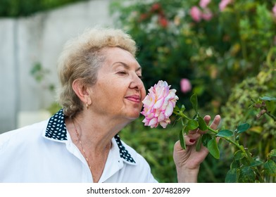 Nice elderly woman smelling flower in the garden on a warm autumn day. Enjoying life after retirement. Lifestyle image of grandmother in the garden living a stress free life