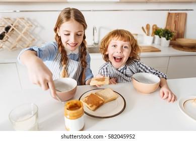 Nice energetic children enjoying their morning meal