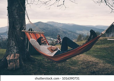 Nice evening. Handsome young man lying in hammock and smiling while camping with his girlfriend