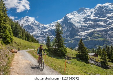 nice and ever young senior woman riding her e-mountainbike below the Eiger northface, Jungfrauregion, Switzerland