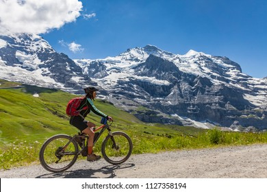 nice and ever young senior woman, riding her e Mountainbike in the Jungfrauregion of the swiss alps, high above Grindelwald and Wengen