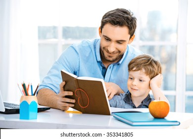 Nice family photo of little boy and his father. Boy and dad sitting at room with big window. Young man helping his son to make homework