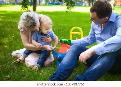 nice family walking in city park, sweet couple with their little son have rest in park, concept of happy family