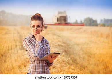 Nice farmer wooman in glasses with hair tied in a ponytail standing with tablet and thinking in wheat field while combine harvesting in background. Horizontal. Image released.