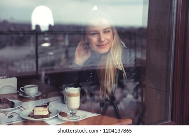 Nice female in cafe in warm cozy atmosphere, enjoying view through the window, casual urban life of young people