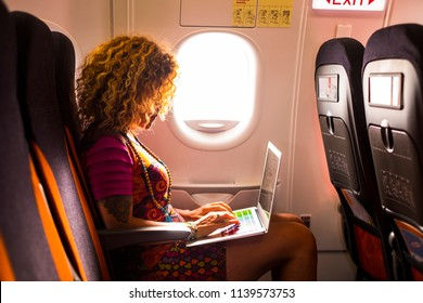 nice female with curly hair sitting inside the airplane ready to flight for the nex destination use a laptop during the trip. work or pleasure activity for beautiful middle age woman traveler.