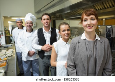 Nice female manager posing with the staff in a professional kitchen