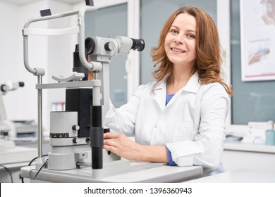 Nice female oculist checking eyesight with slit lamp in clinic. Professional eyes doctor in white uniform sitting at table, looking at camera and smiling in optical shop. Concept of eye care.