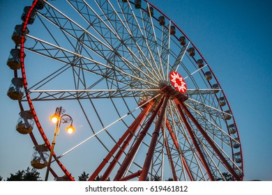 Nice Ferris wheel in late evening with beautiful lights in a park
