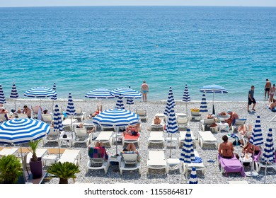 NICE, FRANCE -26 MAY 2018- View of umbrellas and lounge chairs with blue and white stripes on the pebble beach below the Promenade des Anglais along the Mediterranean Sea in Nice, French Riviera.