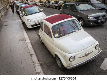 Nice, France - April 2010: Two white convertible cabrio Fiat 500 Abarth with maroon plum sunroof, modern and vintage next to each other, same color. Old and new car concept