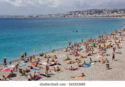 NICE, France  - August 19, 2014: Crowded pebble beach in Nice, France, in front of a turquoise blue sea