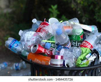 Nice, France - August 5, 2019: An overflowing trash can in Nice, France. Plastic bottles, paper bags, food containers and soda cans