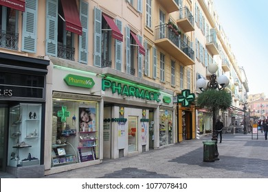 NICE, FRANCE - FEBRUARY 03, 2016; Local French pharmacy on walking street in Nice with glowing sign and people in the back. Pharmacies in France are the only stores licensed to sell prescription drugs