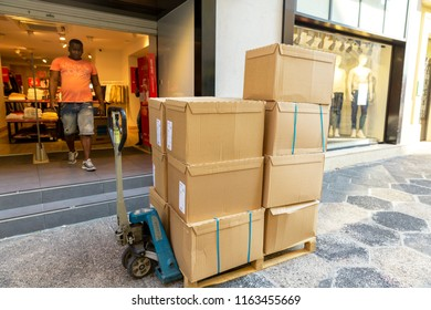 Nice, France, July 06, 2018: Healthy lifestyle in an urban environment. The worker unloads the boxes with the goods to the store.