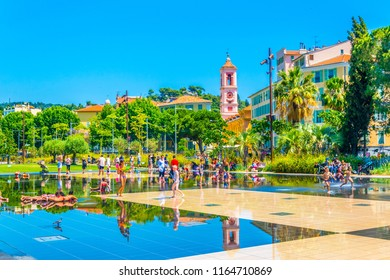NICE, FRANCE, JUNE 11, 2017: Kids are playing inside of a fountain at the park promenade du paillon in Nice, France