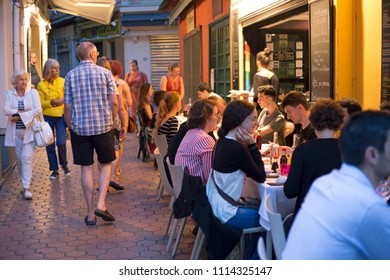 Nice, France, June 2018, Tourists walk amongst diners at pavement cafe's in the early evening.