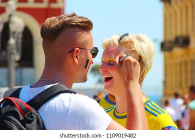 NICE, FRANCE - JUNE 22, 2016: Football fans painting faces at the day of UEFA EURO 2016 game Belgium vs Sweden